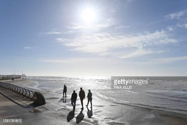 People enjoy the sunshine as they walk along the beach near the Blackpool Pleasure Beach amusement park in Blackpool, Lancashire on March 16, 2021.