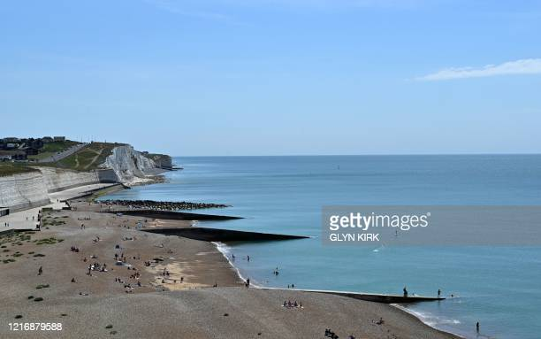 People enjoy the sunshine at Saltdean beach near Brighton on the south coast of England on June 2 2020 following a further relaxation of the novel...