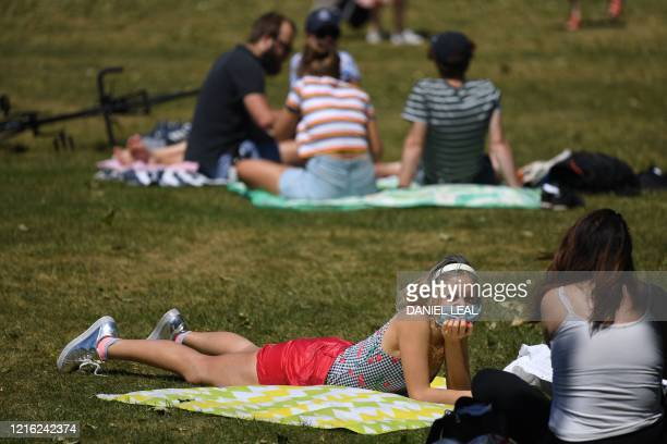 People enjoy the sunshine at St James Park in central London on May 30 as lockdown measures are eased during the novel coronavirus COVID-19 pandemic....