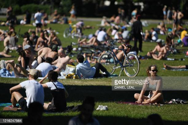 People enjoy the sunshine at Victoria Park in east London on May 30 ahead of the coming into force of the first significant easing of Britain's...