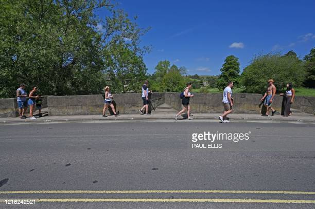 People enjoy the sunshine by the River Wye at Bakewell in the Peak District National Park in northern England on May 30, 2020 after the announcement...