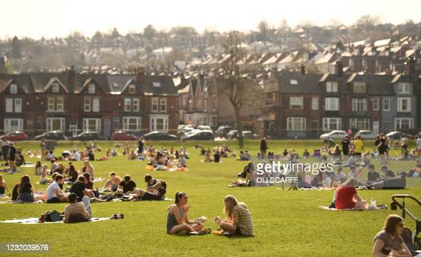 People enjoy the sunshine in Endcliffe Park in Sheffield, northern England, on March 31, 2021 as England's third Covid-19 lockdown restrictions eased...