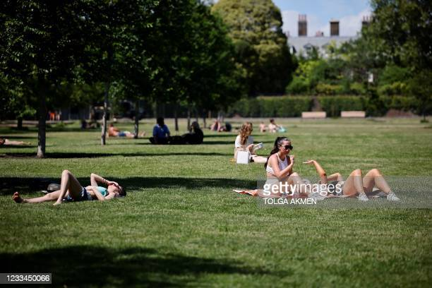 People enjoy the sunshine in Hyde Park in London on June 14, 2021. - Britain was on Monday widely expected to delay the full lifting of coronavirus...