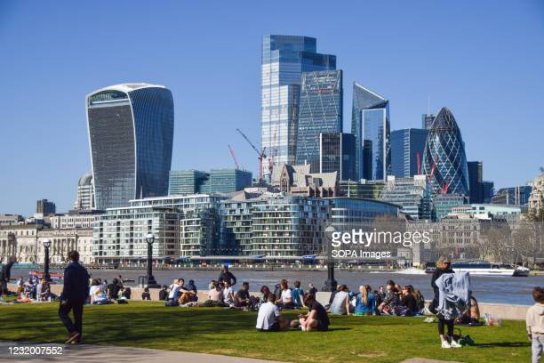 People enjoy the sunshine in Potters Fields Park next to Tower Bridge with a view of the City of London. People flock outdoors on a warm day as...