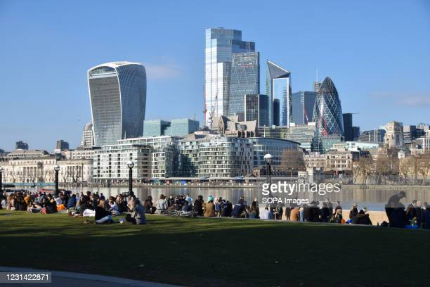 People enjoy the sunshine in Potters Fields Park with a view of the City of London skyline. The coronavirus alert level has dropped in England,...