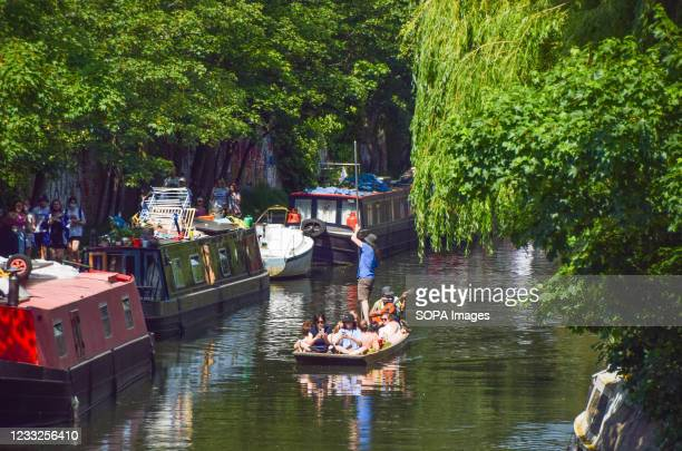 People enjoy the sunshine on a boat on Regent's Canal in Primrose Hill as the heatwave continues in London.