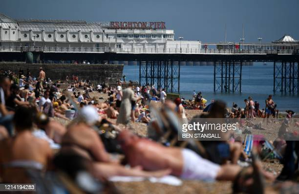 People enjoy the sunshine on the beach in Brighton, on the south coast of England on May 20 the hottest day of the year so far. - England's official...