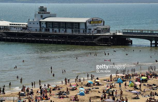 People enjoy the sunshine on the beach near Bournemouth Pier in Bournemouth, southern England on May 25 after some lockdown restrictions put in place...