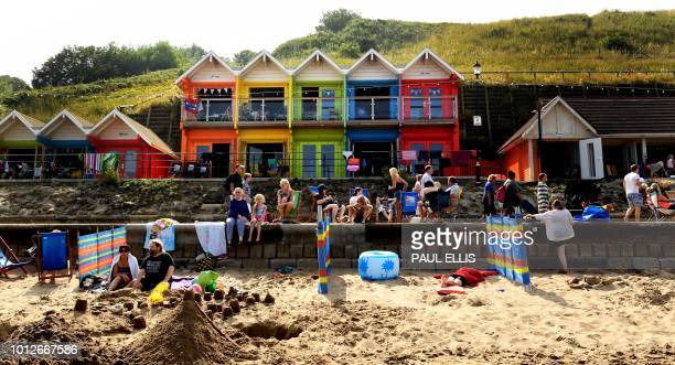 People enjoy the sunshine outside coloured beach huts at North Bay, Scarborough, northern England, on August 7, 2018 as Europe continued to swealter...
