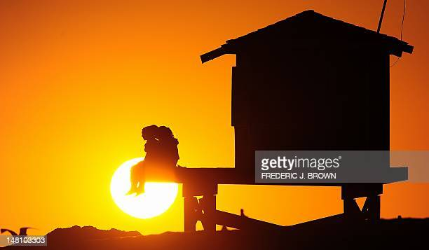 People enjoy the view from a lifeguard structure as the sun sets at Seal Beach south of Los Angeles California on July 9 2012 Much of the US has been...
