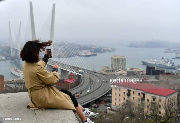 People enjoy the view from an observation point in the far-eastern Russian port of Vladivostok on April 23, 2019. - North Korean leader Kim Jong Un...