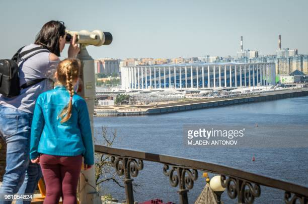 People enjoy the view from an observation point with the Nizhny Novgorod Arena seen in the background in Nizhny Novgorod on May 21 2018 Nizhny...