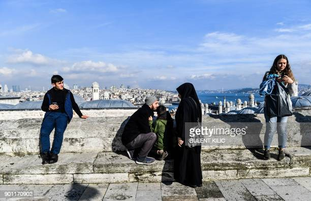 People enjoy the view of The Bosphorus from a terrace of Mimar Sinan Mosque as the sun shines in Istanbul on January 4 2018 / AFP PHOTO / Bulent Kilic