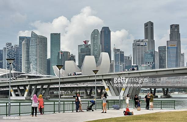 People enjoy the view of the city skyline along Marina Bay in Singapore on March 3 2015 AFP PHOTO / ROSLAN RAHMAN