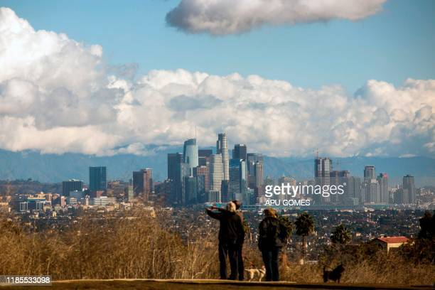 People enjoy the view of the downtown Los Angeles skyline with the snowcovered San Gabriel Mountains in the background on November 29 2019 in Los...