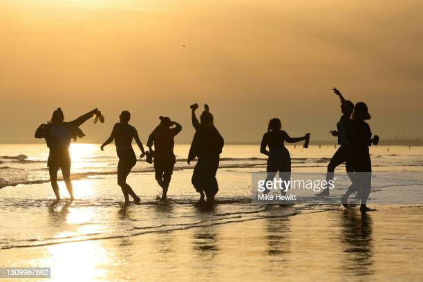People enjoy the warm Spring weather and low tide on Brighton beach on March 30, 2021 in Brighton, United Kingdom.