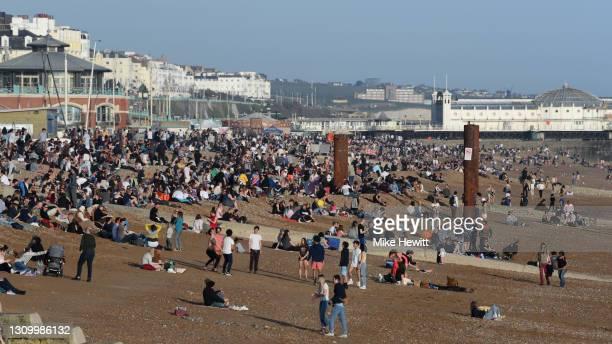 People enjoy the warm Spring weather on Brighton beach on March 30, 2021 in Brighton, United Kingdom.