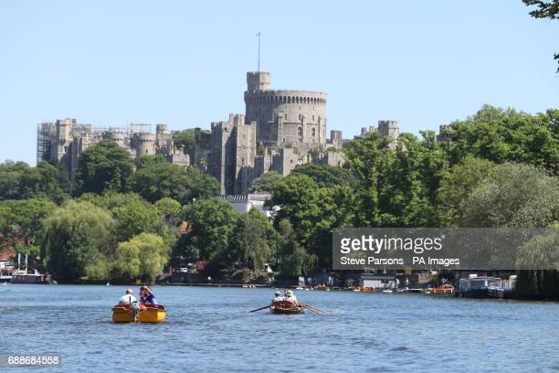 People enjoy the warm weather as they row on the River Thames near Windsor Castle as Britons hoping for a scorching bank holiday may be disappointed...