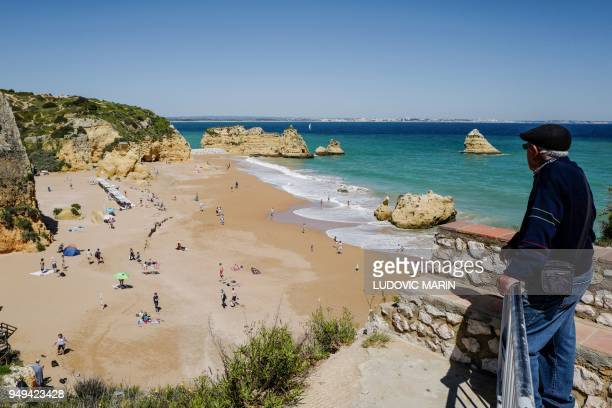People enjoy the warm weather at the Dona Ana beach in Lagos on April 18 2018 in the southern Portugal region of Algarve