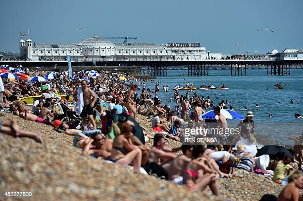 People enjoy the warm weather on Brighton beach in Sussex southern England on July 17 2014 Britons were sent scampering for shade as the temperature...