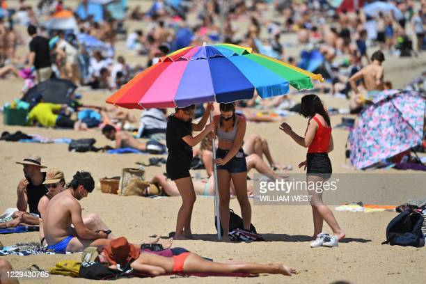 People enjoy the warm weather on Melbourne's St Kilda Beach on November 3 as Australia's Victoria state records its fourth straight day of zero...