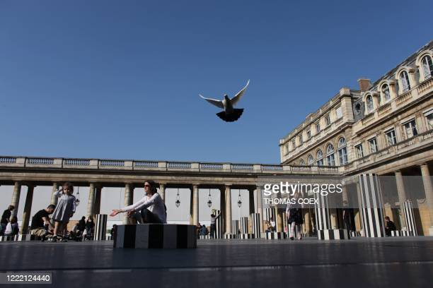 People enjoy the warm weather on the Buren Columns at the Palais Royal garden on April 18 2010 in Paris