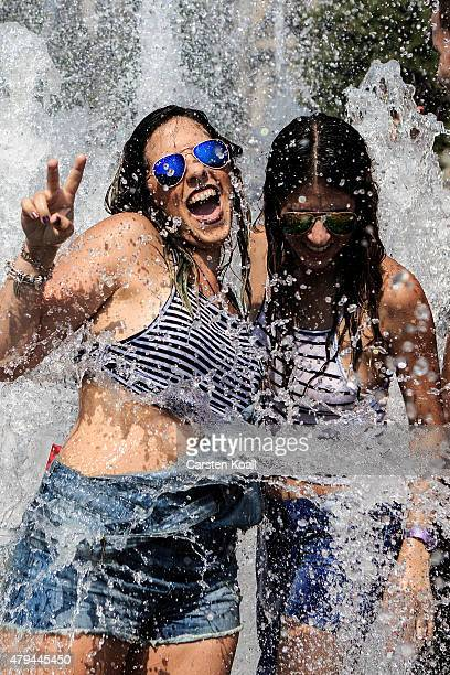 People enjoy the water fountain in the landmark Lustgarten during a sweltering summer day on July 4 2015 in Berlin Germany Temperatures were expected...