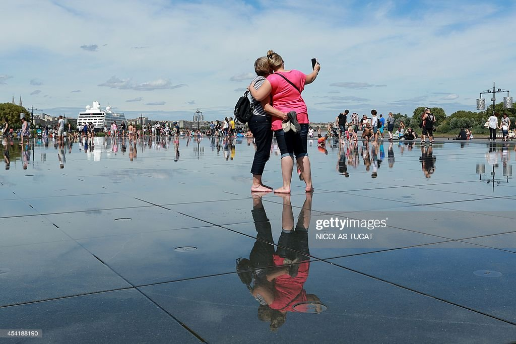People enjoy the Water Mirror on August 25, 2014 in the southwestern French city of Bordeaux. Hardly eight years after its creation, the Water Mirror is taking an amazing place in the daily lives of Bordeaux residents.