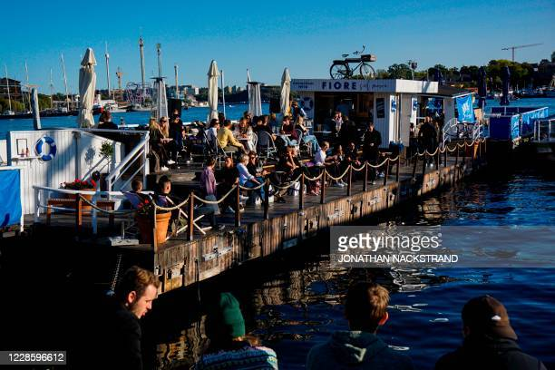 People enjoy the weather on a floating bar at Stranvagen in Stockholm on September 19 during the novel coronavirus COVID-19 pandemic.