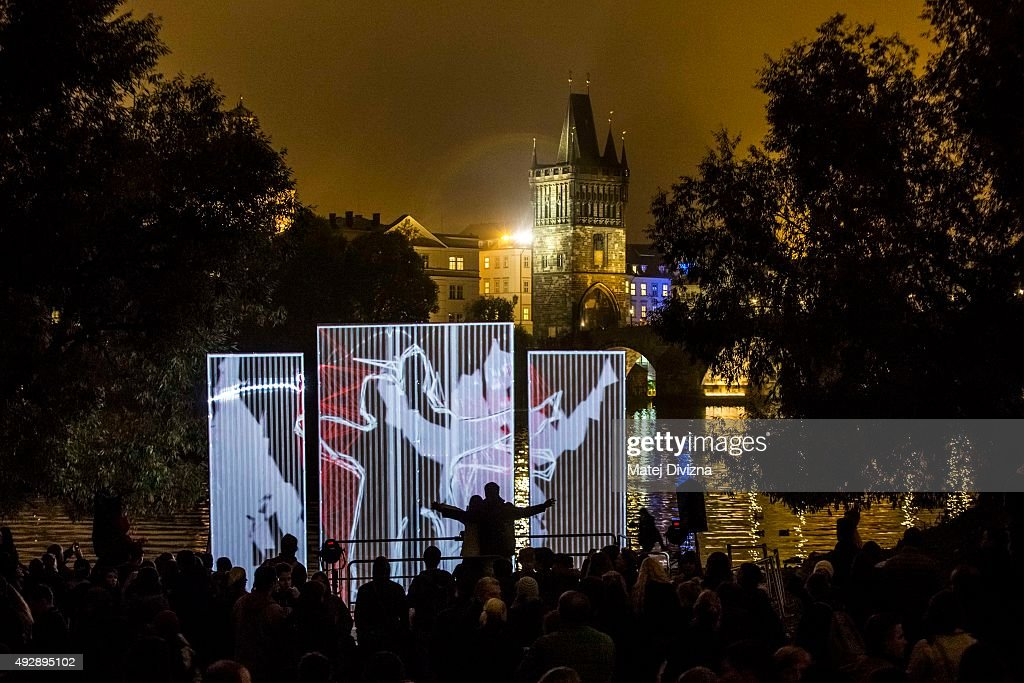 People enjoy the 'Wide/Side' installation by Joao Martinho Moura during the Signal light festival on October 15, 2015 in Prague, Czech Republic. Local and international artists present news in videomapping, site-specific projections, interactive and light installations in the streets of the city during four day festival.