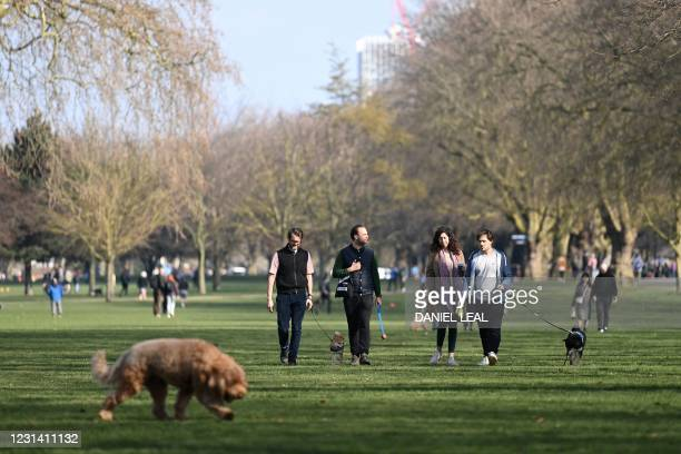 People enjoy the winter sunshine as they take walk their dogs in Victoria Park, east London on February 27, 2021.