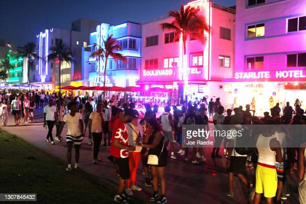 People enjoy themselves as they walk along Ocean Drive on March 18, 2021 in Miami Beach, Florida. College students have arrived in the South Florida...