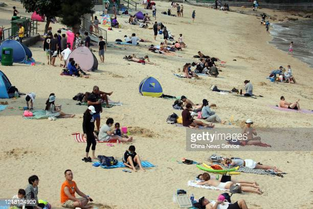 People enjoy themselves on a beach at Stanley seaside village during the 3day Easter holiday amid the coronavirus outbreak on April 10 2020 in Hong...