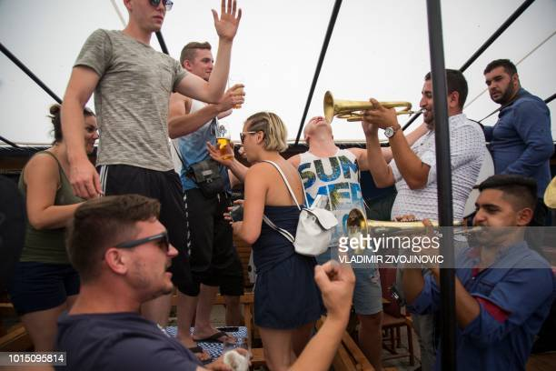 People enjoy trumpet music during the trumpet and brass band festival in the Serbian village of Guca about 160 km south of Belgrade on August 11 2018...