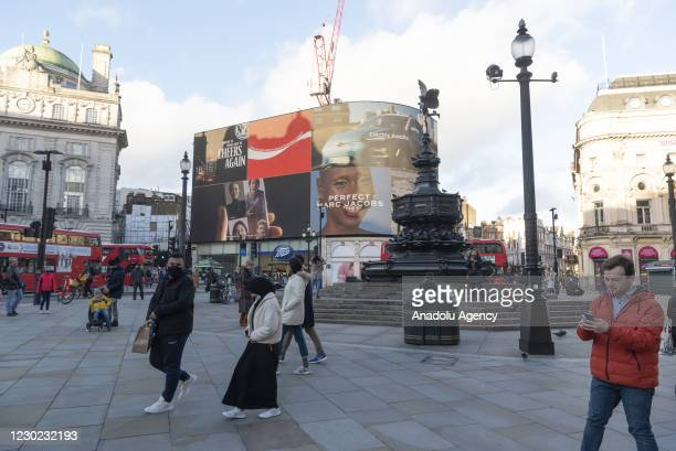 People enjoy walking around Piccadilly Circus as London was placed in Tier 4 measurements starting today due to the rapid rise of Covid-19 infections...