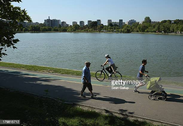 People enjoy warm weater at Lacul Titan lake in Titan district on September 7 2013 in Bucharest Romania While the Romania's economic output has risen...