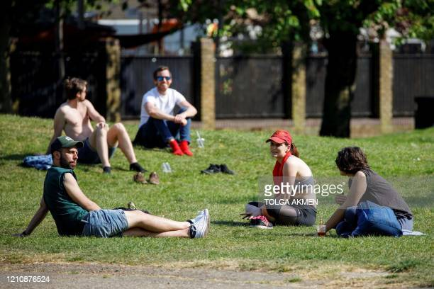 People enjoy warm weather at London Fields in east London on April 24 during the national lockdown due to the novel coronavirus COVID-19 pandemic. -...