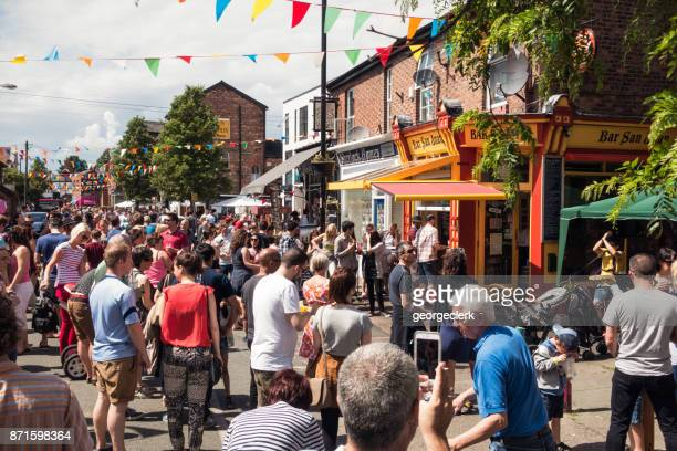 people enjoying a street festival in chorlton, manchester - manchester uk stock photos and pictures