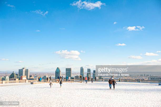 people enjoying a sunny winter day at the top of mont-royal public park covered in snow with downtown montréal on the background - montreal stock pictures, royalty-free photos & images