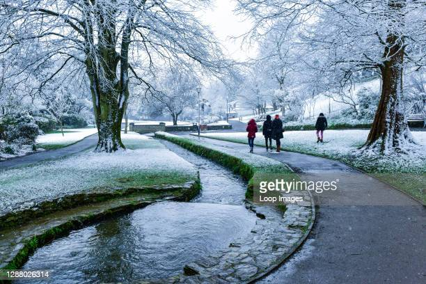 People enjoying a walk in the snow in Trenance Gardens in Newquay in Cornwall.