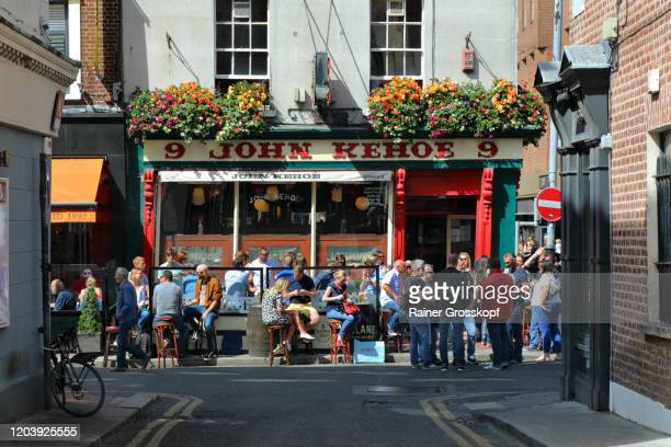 people enjoying a warm sunny day in front of a typical pub in the heart of dublin - rainer grosskopf stock pictures, royalty-free photos & images