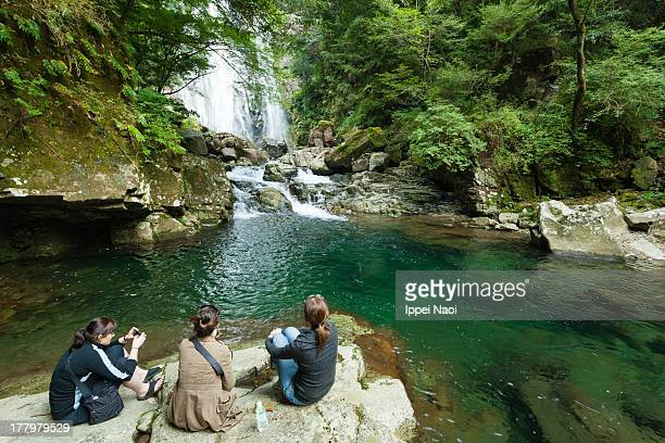 People enjoying a waterfall in forest, Japan
