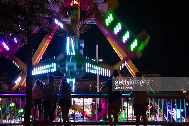 People enjoying and have fun in a Fun Fair attractions at night with motion