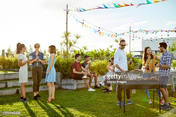 people enjoying asado party at backyard - barbecue grill stock pictures, royalty-free photos & images