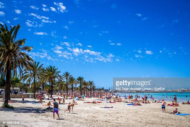 people enjoying at beach against blue sky - palma majorca stock photos and pictures