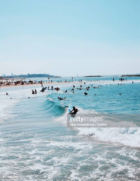 people enjoying at beach against clear sky - tel aviv stock photos and pictures