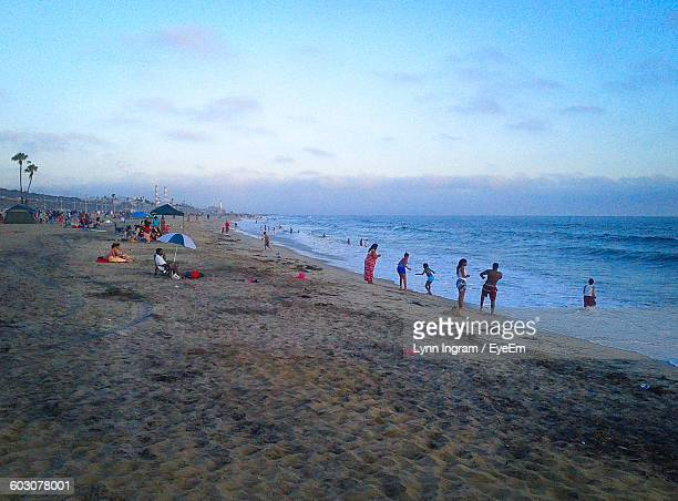 people enjoying at beach against sky - lynn pleasant stock pictures, royalty-free photos & images