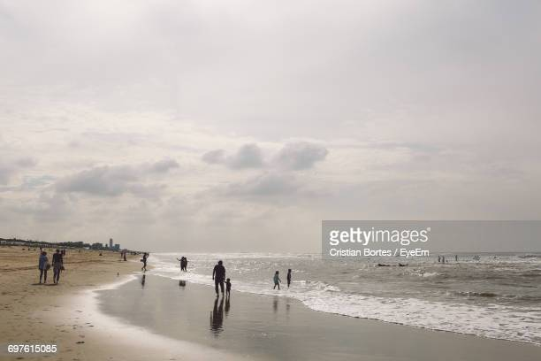 people enjoying at beach against sky - bortes foto e immagini stock