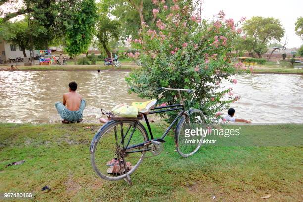 people enjoying at canal site in hot temperature - amir mukhtar stock photos and pictures
