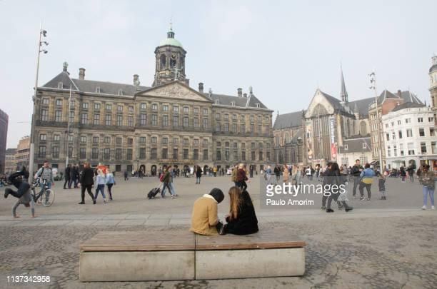 people enjoying at dam square in amsterdam - koninklijk paleis amsterdam stockfoto's en -beelden